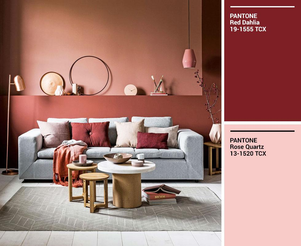 A living room with a pale sofa set against a terracotta wall, with pink and orange accents.