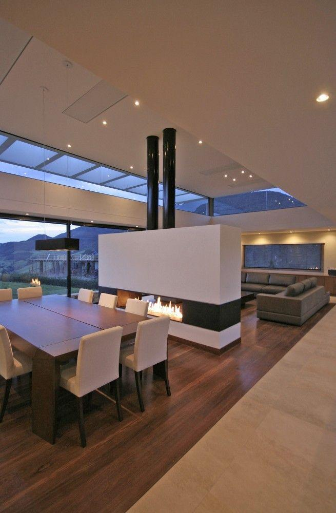 Modern fireplace that separates the dining room from the living room.