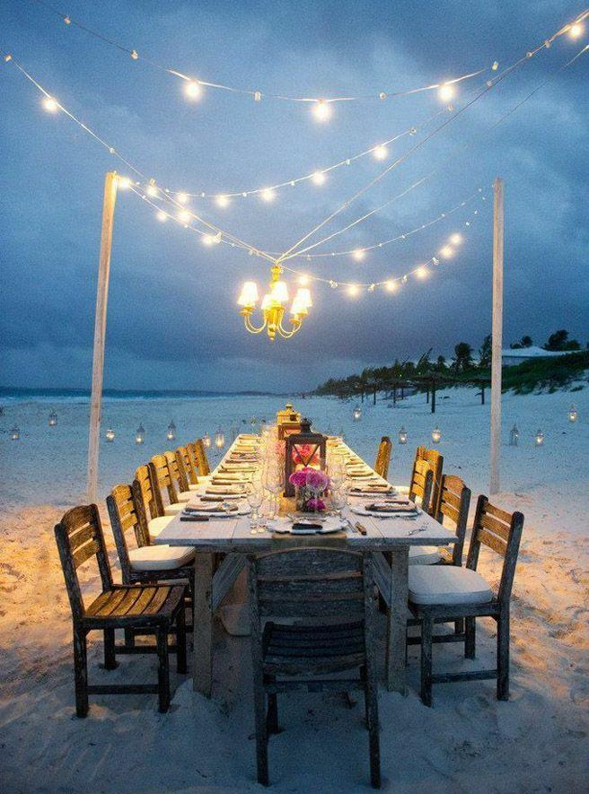Long dining table by the beach with fairy lights.