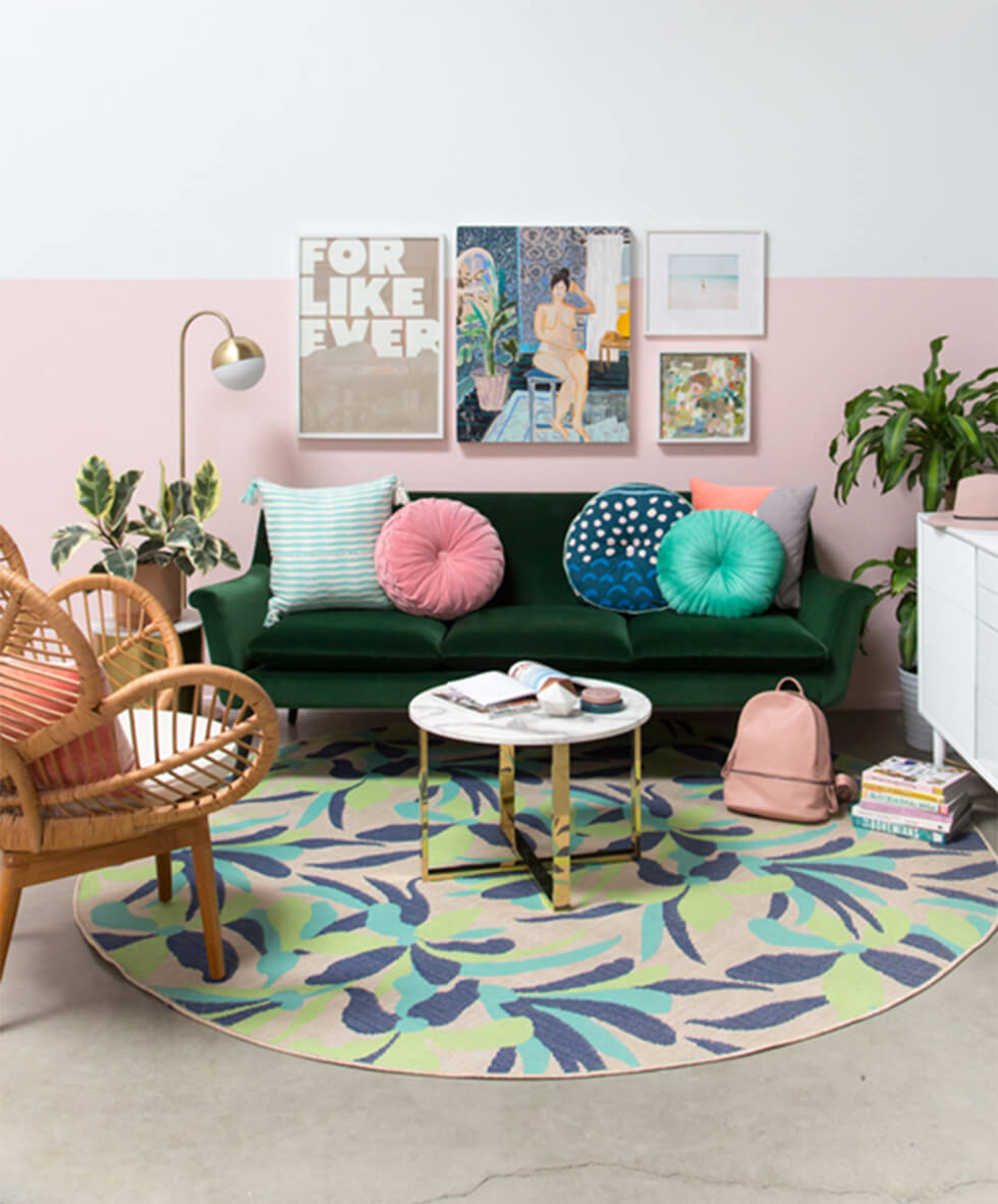 Colourful bohemian living room with green sofa, pastel cushions and rug