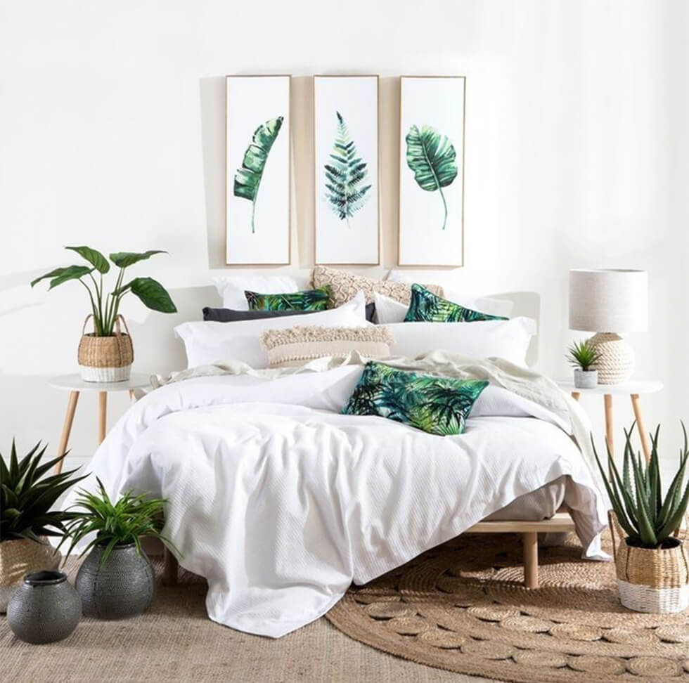 White minimalist tropical bedroom with indoor plants and accessories