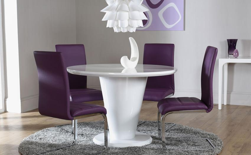 Round white pedestal dining table with four purple dining chairs.