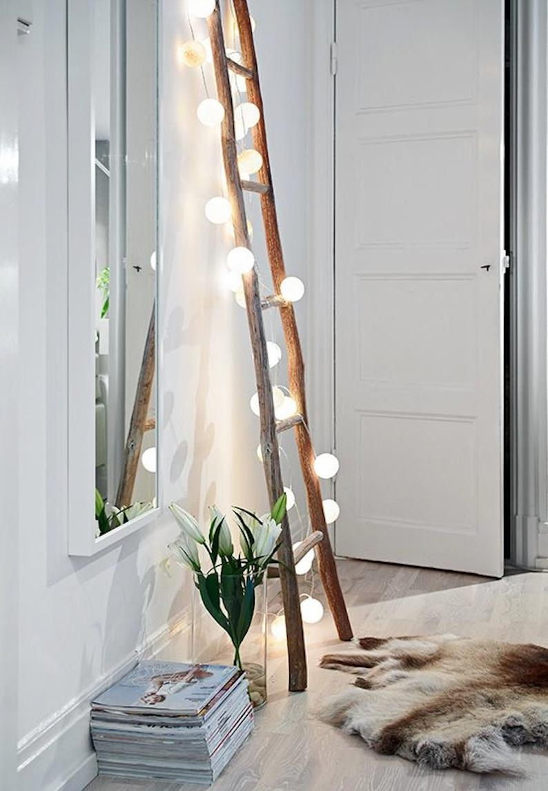 Wooden ladder with lights against a white wall.