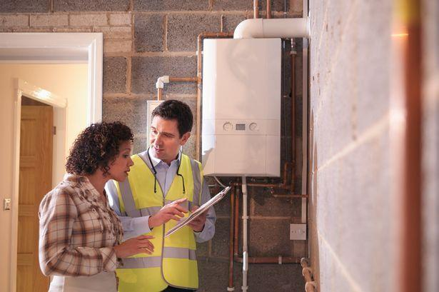 Woman consulting male technician next to the boiler.