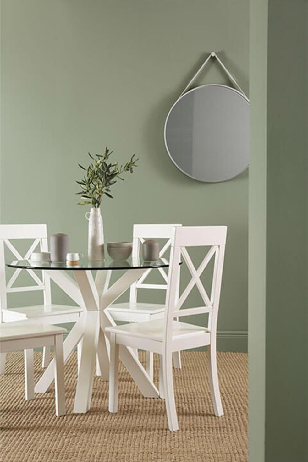 round white and glass dining table in a contemporary sage green dining room