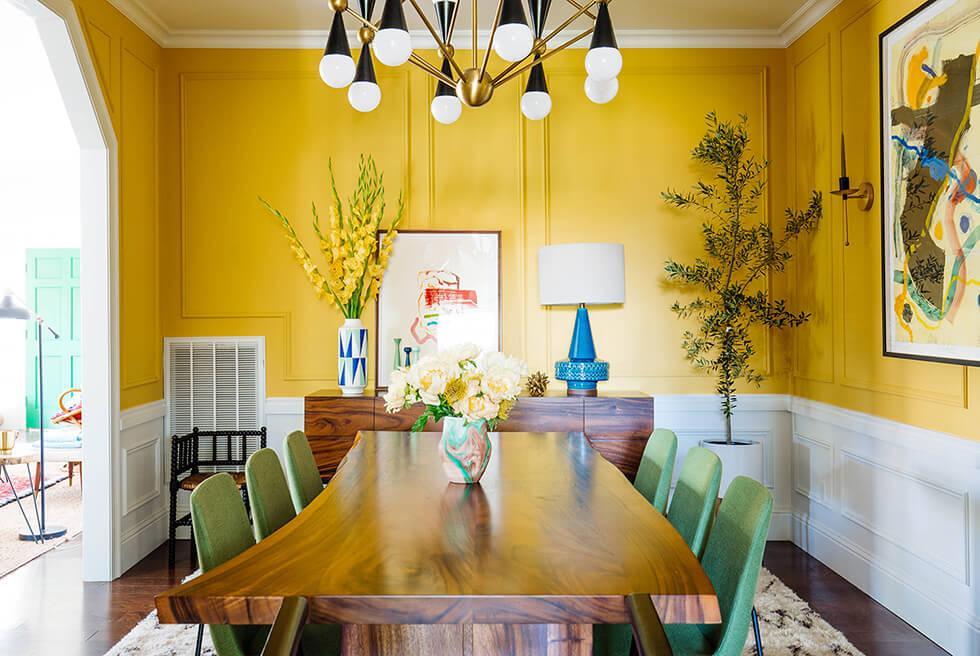 mustard yellow half wall in a modern artsy dining room