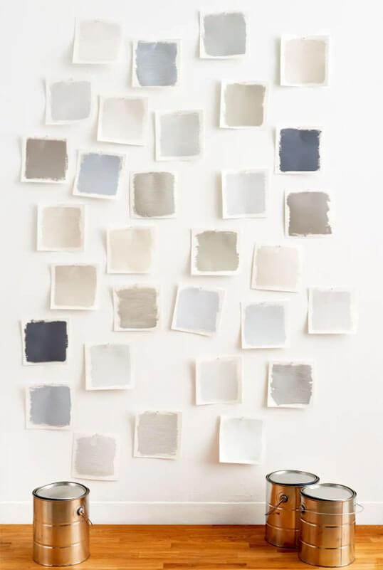 Paint swatches of different grey shades on a wall.
