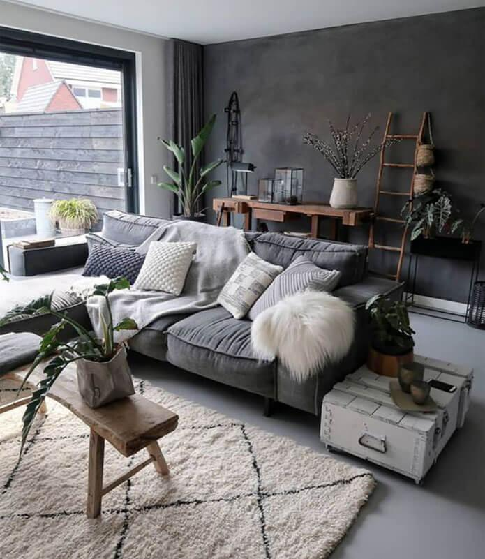 Grey living room with plants and a grey sofa with pillows and throws.