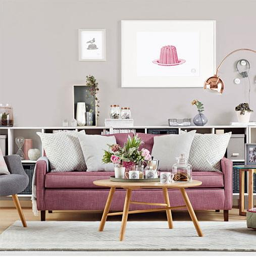 Light grey sofa in a light pink room.