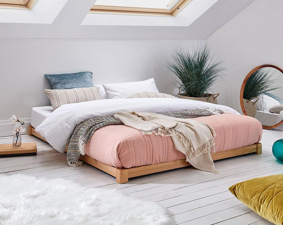 Loft bedroom with coral bedding that has a tropical vibe