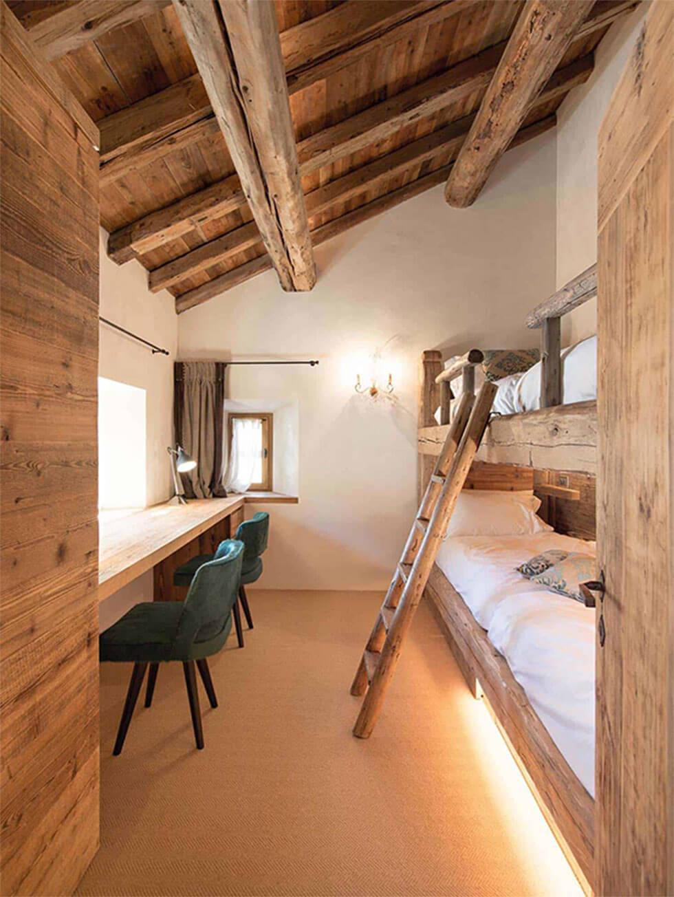 Classic wooden loft bedroom with bunk beds and wooden writing desk