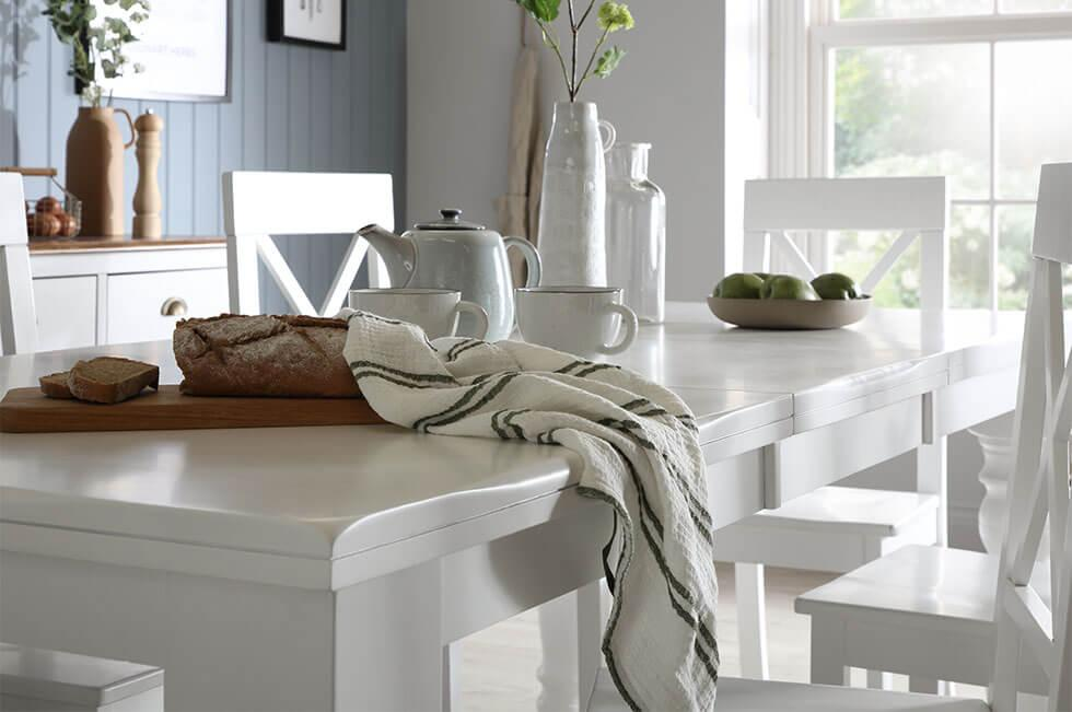 Close up of a white wooden extending dining table with matching chairs and blue walls