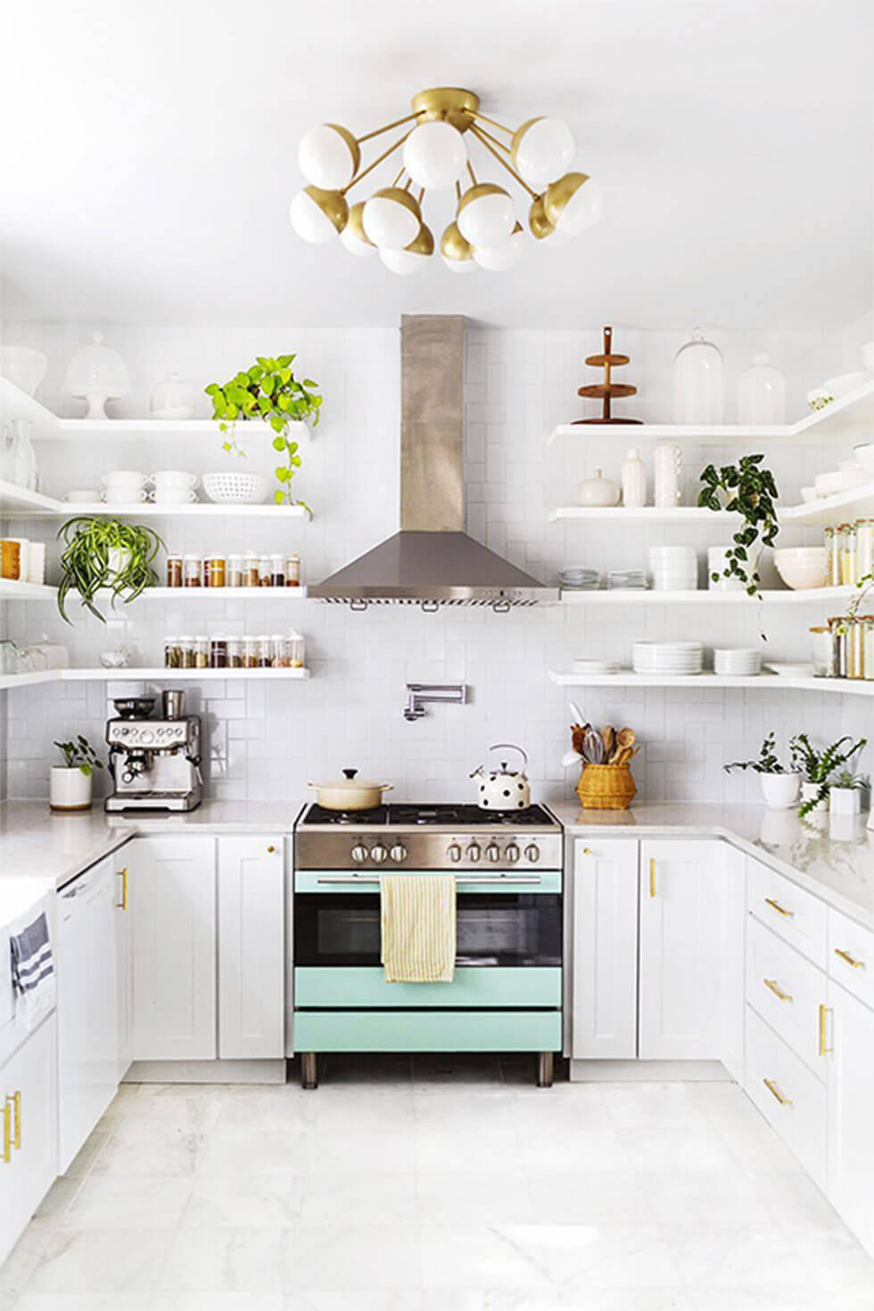 Small white kitchen with shelves on walls, a light blue oven, and a statement gold lamp