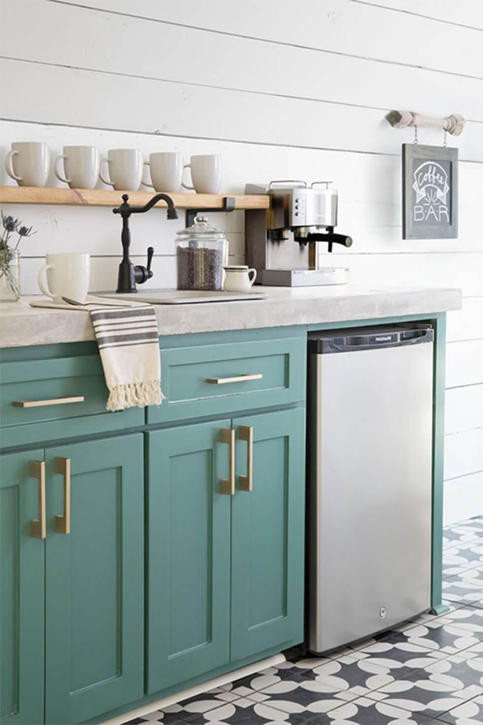 Simple white small kitchen with shiplap walls, teal cabinets with gold handles, and geometric floor tiles