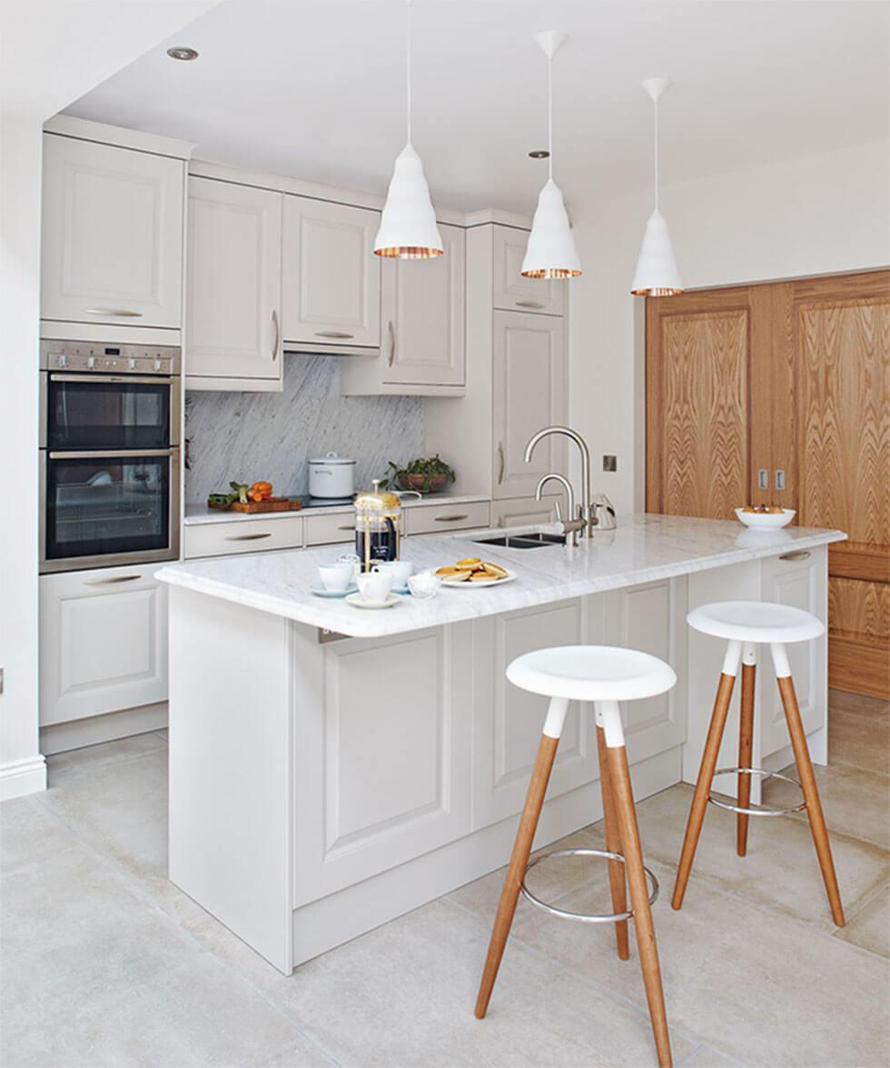 Airy white small kitchen with a kitchen island, wooden bar stools and a tall cupboard