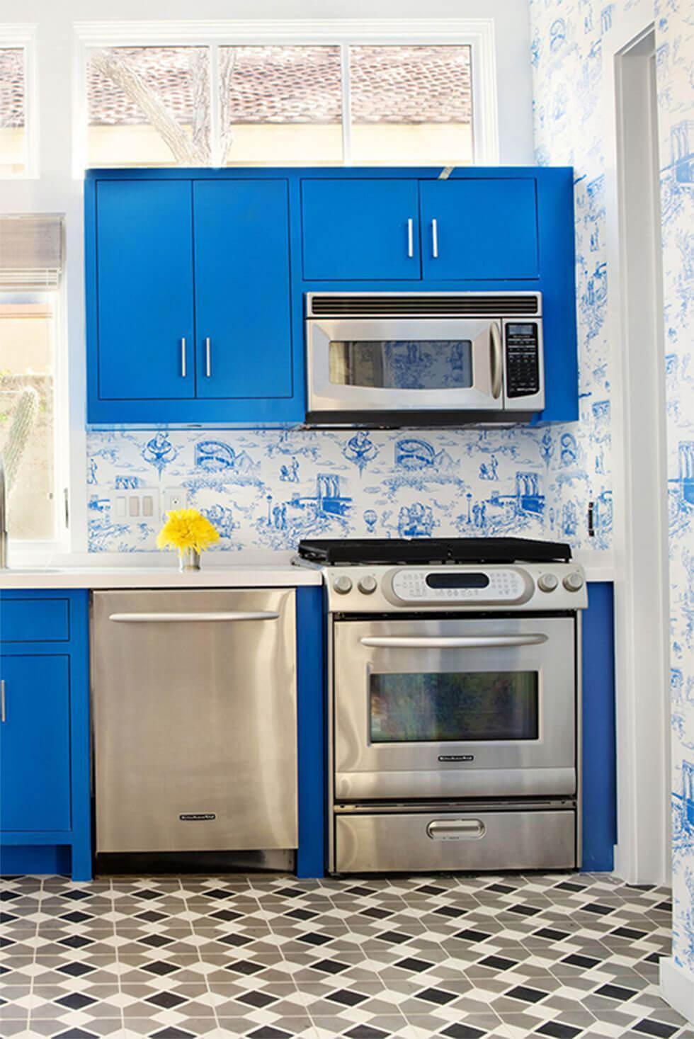 Small kitchen with statement blue cabinets, chrome appliances, geometric tiles and blue floral wallpaper