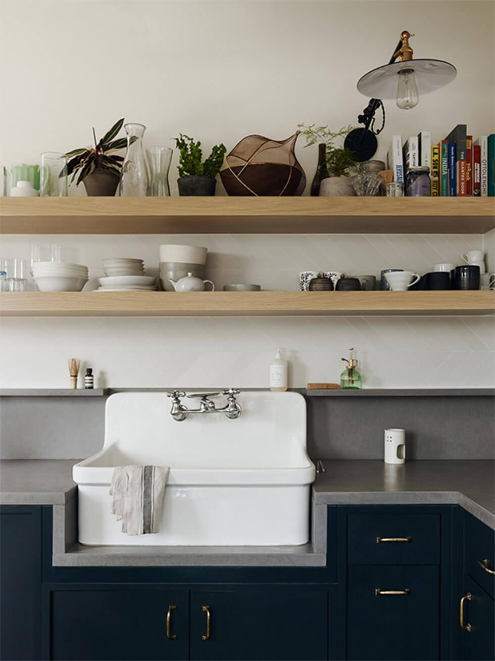 Minimal small kitchen with wooden shelves, white sink and dark grey counter tops and cabinets