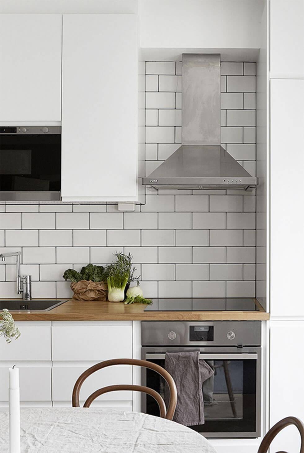 Small kitchen with white cabinets and dining table, subway tile backsplash and chrome cooking hood