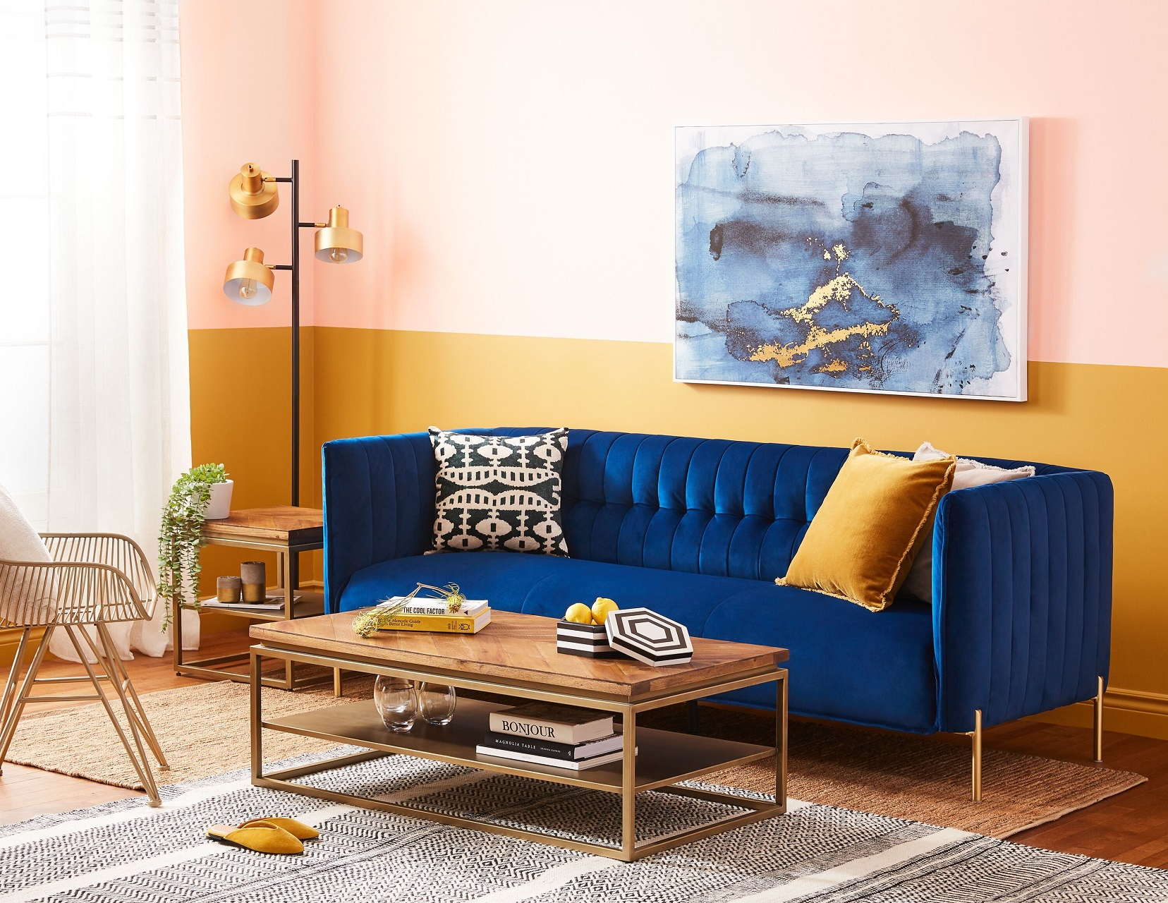 Blue velvet sofa in a contemporary living room with half mustard yellow and pastel pink walls