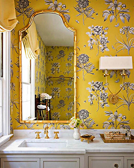 Yellow floral wallpaper in an elegant bathroom with white countertops