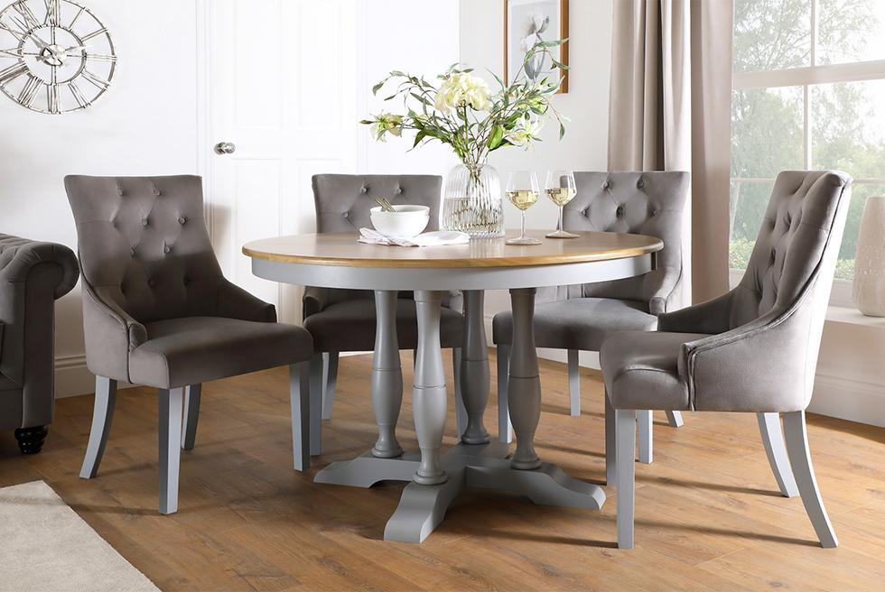 Grey and oak dining table with grey fabric chairs in a well lit contemporary dining room