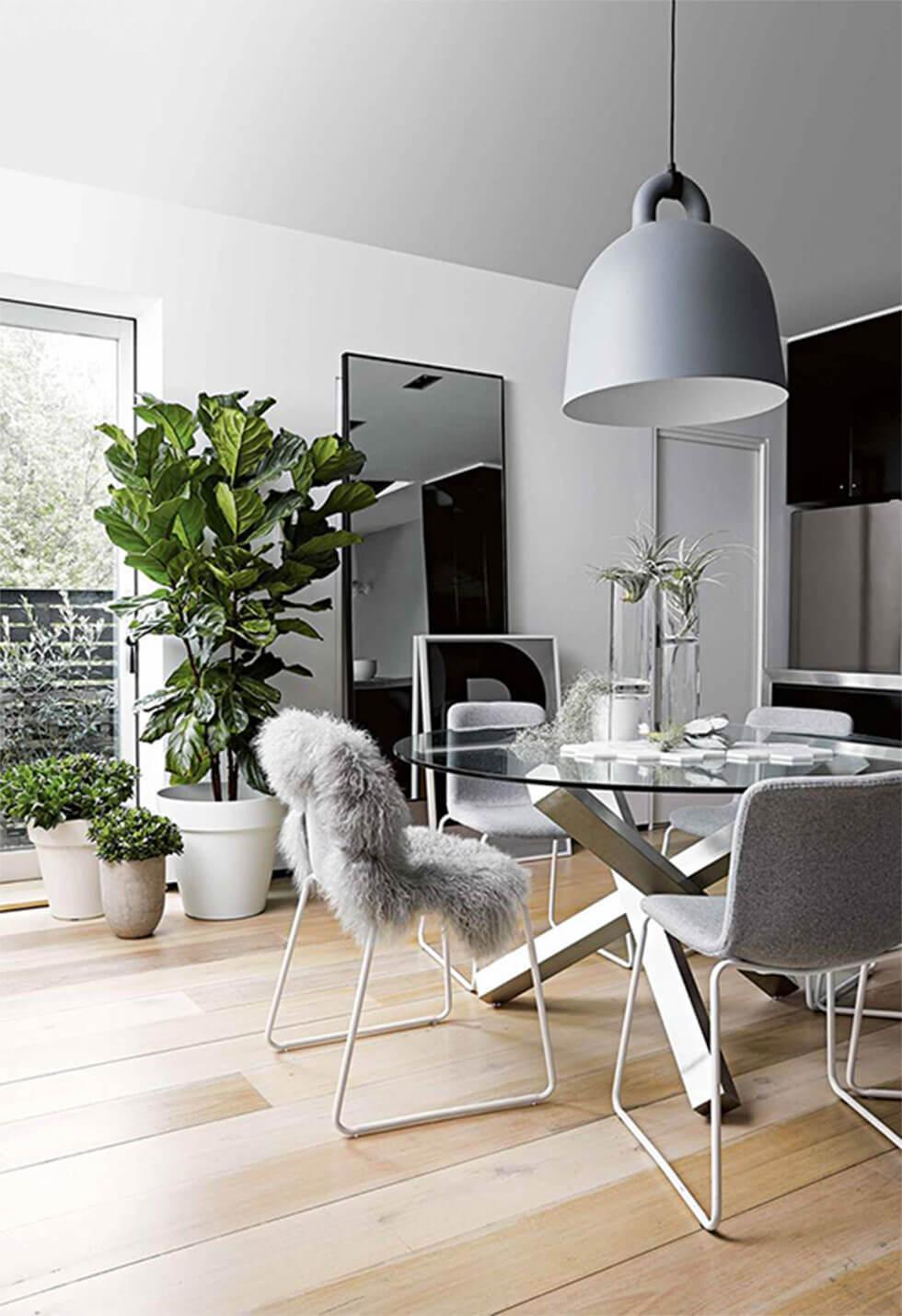 cosy grey dining room with greenery and a faux fur rug