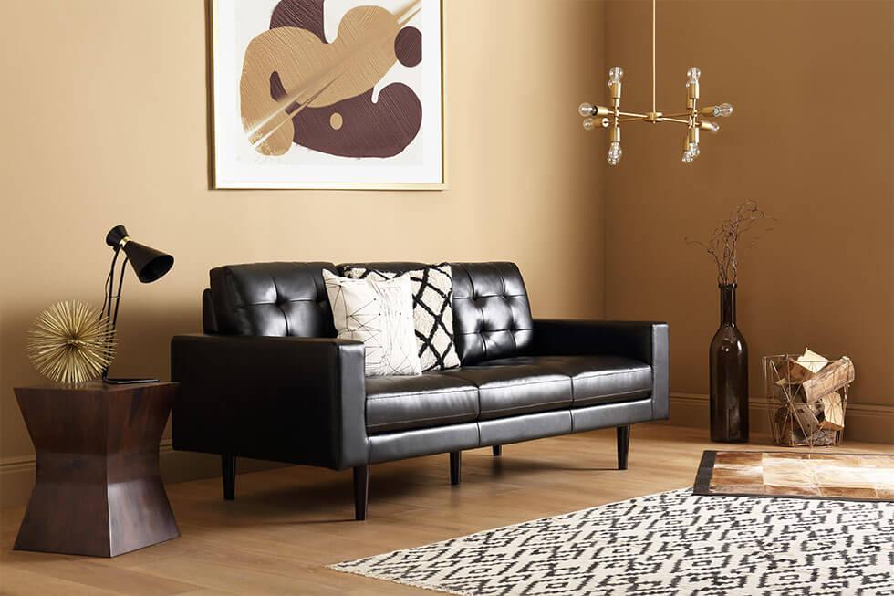 Black leather sofa with caramel walls and parquet flooring.