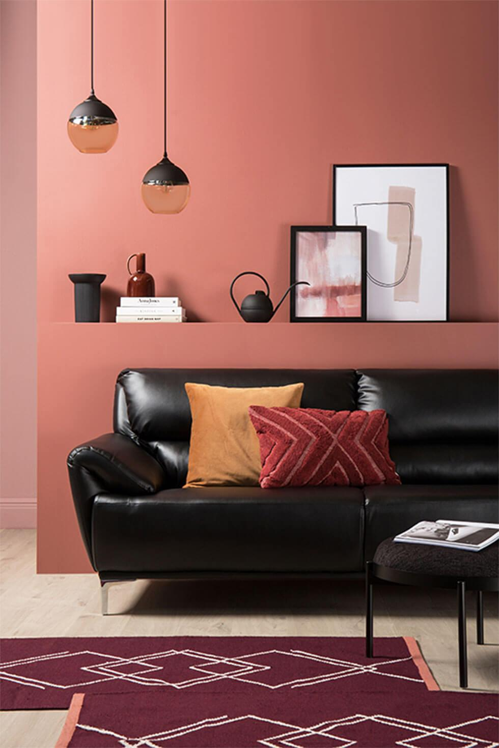 Living room with terracotta walls and black leather sofa