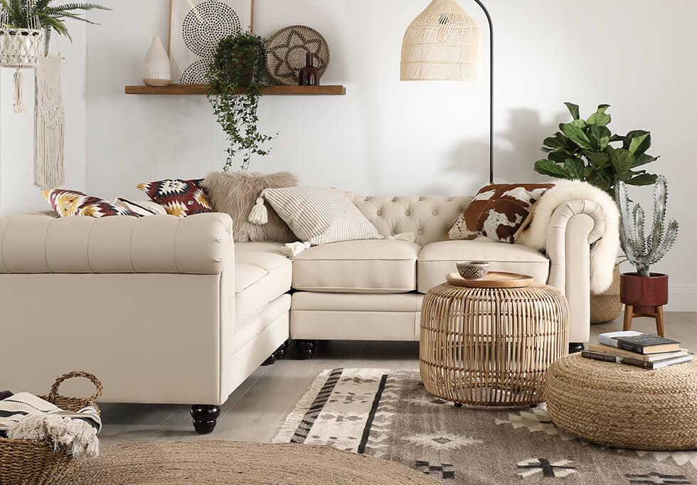Ivory leather chesterfield sofa in a modern boho living room filled with plants