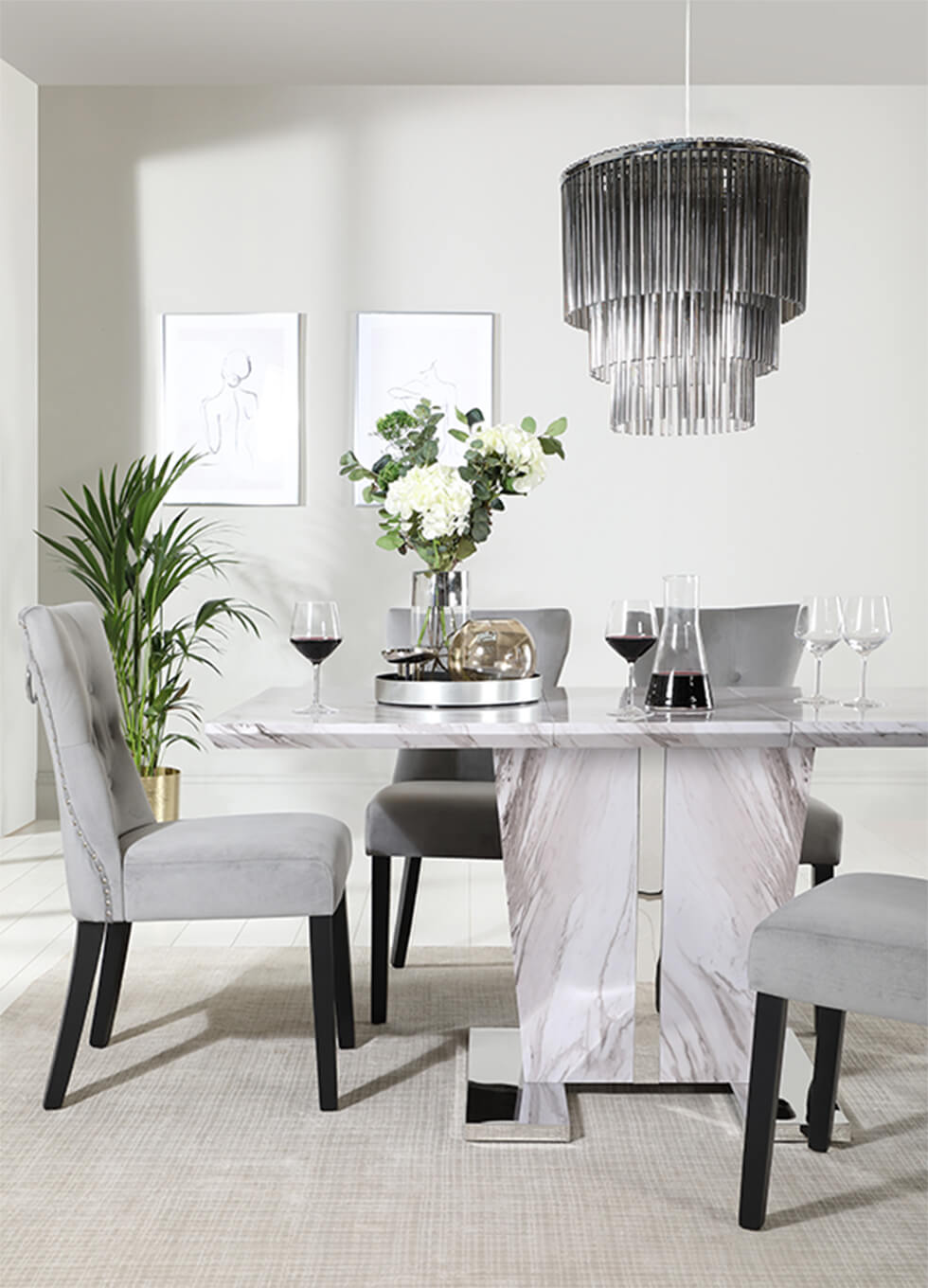 Neutral grey dining room with a grey marble dining table with a pedestal, fringe lamp and indoor plants