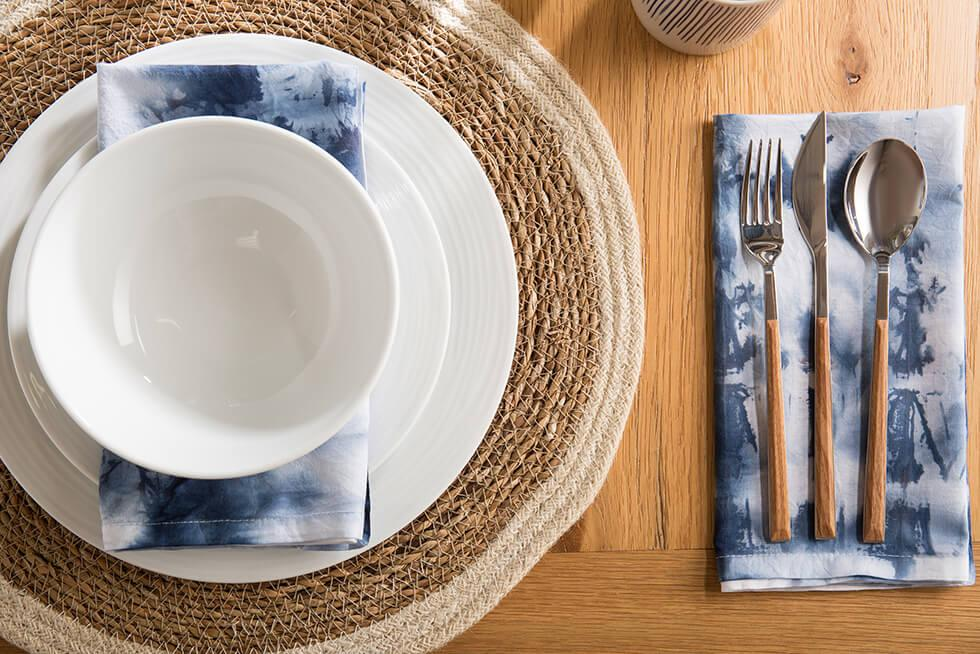 Navy blue shibori tie dye napkins on a wooden dining table