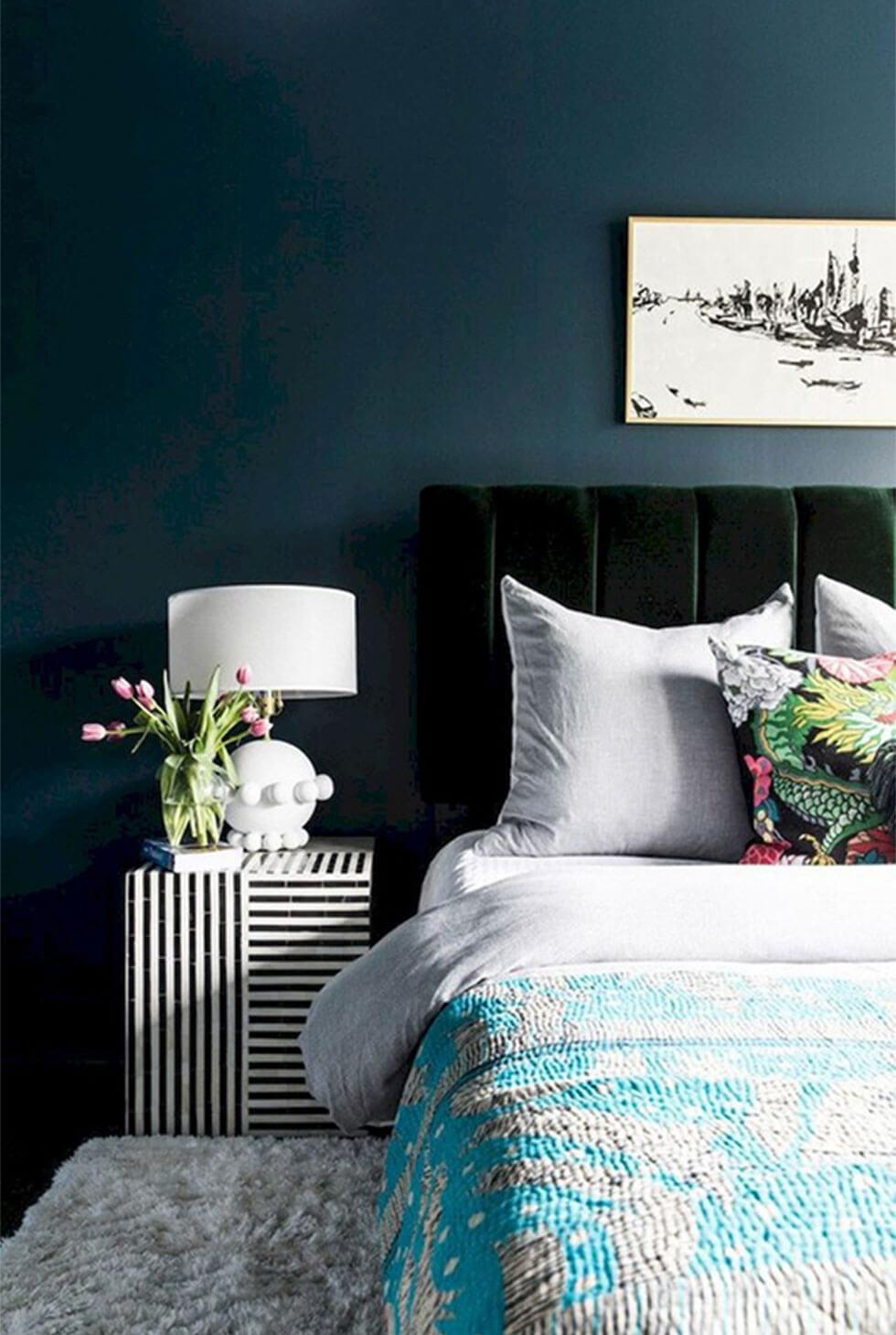 A bedroom wall painted in deep navy blue with an emerald velvet headboard and light coloured bedding.