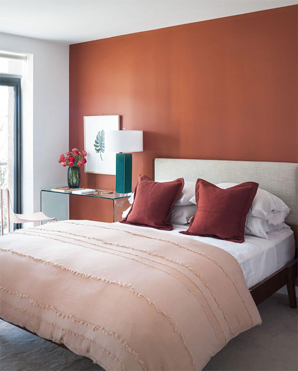 Bedroom with walls painted terracotta with a light neutral bed.
