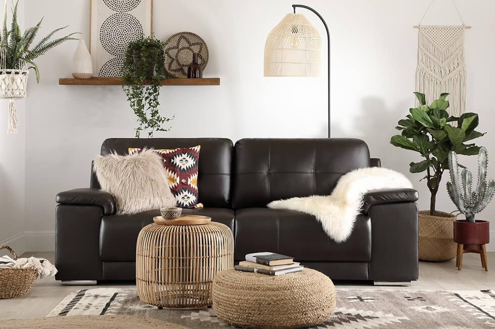 Black leather sofa in a neutral modern boho living room