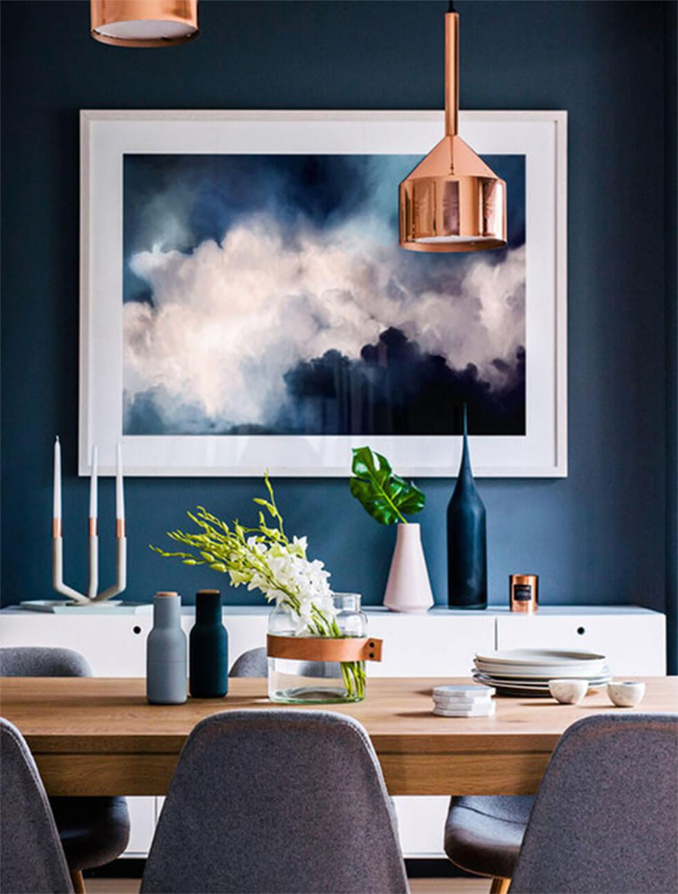 Modern dining room with dark blue backdrop and textured wall hanging