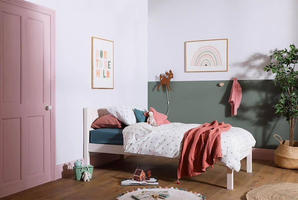 Pink and green kids bedroom with a white wooden bed