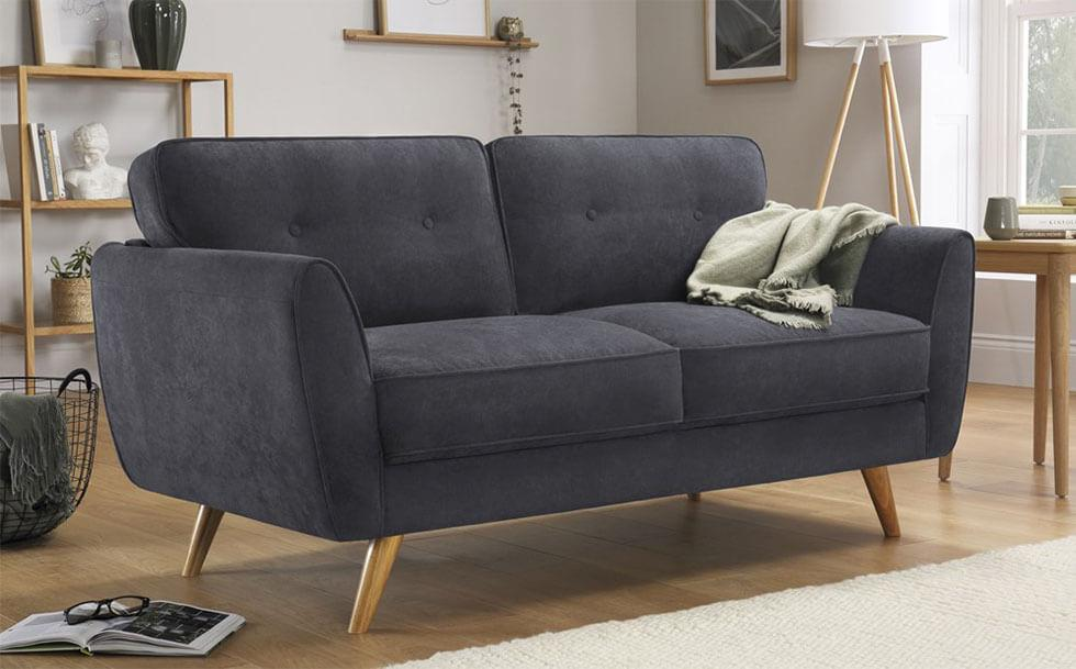 Contemporary grey sofa with wooden legs in a neutral living room.