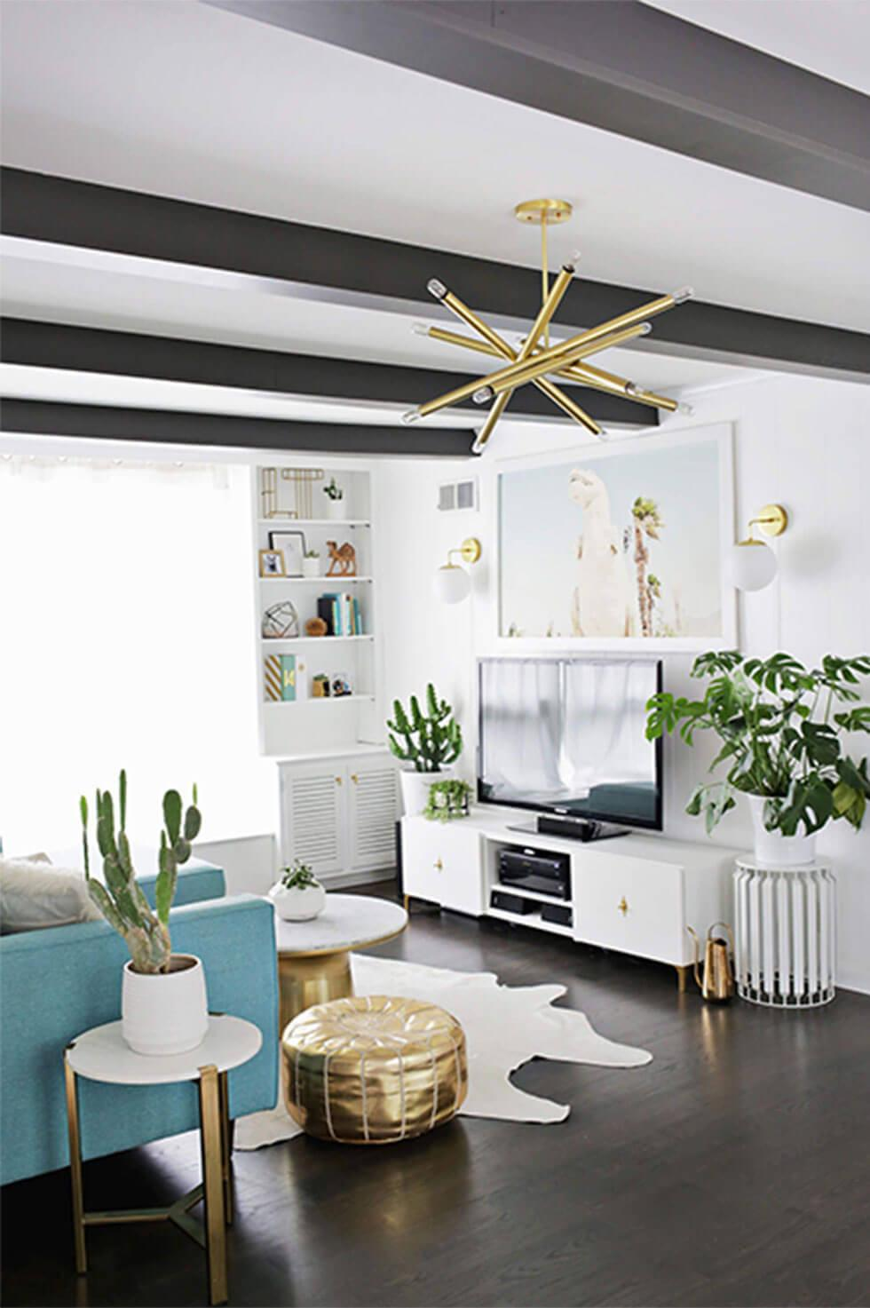 Contemporary living room with cactus plants, gold light fixture, and gold ottoman.