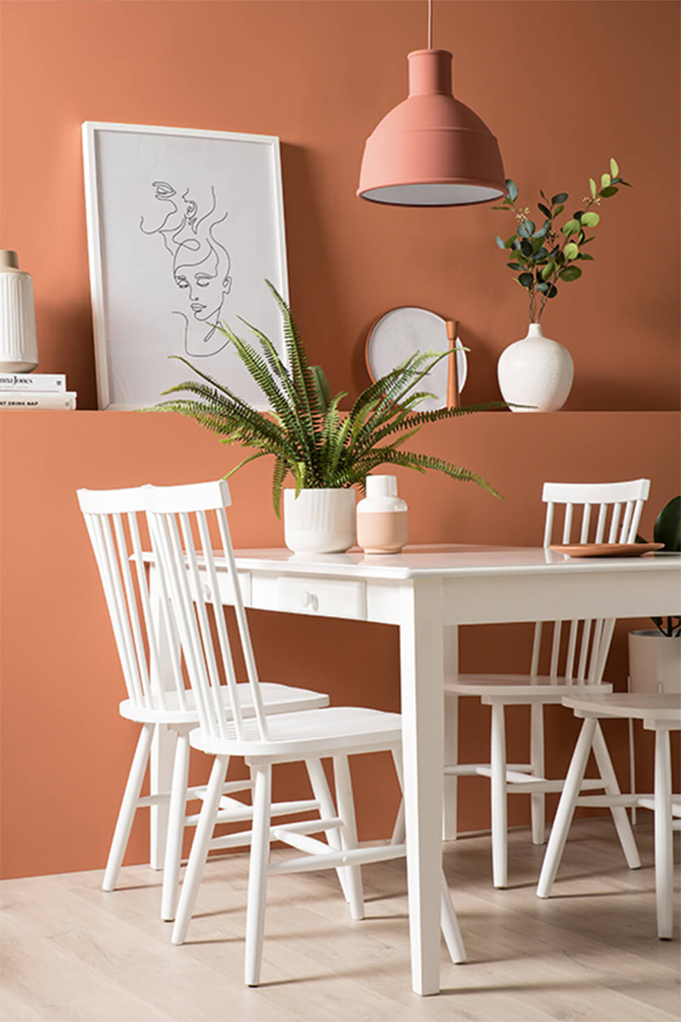 White wooden dining set against terracotta statement wall