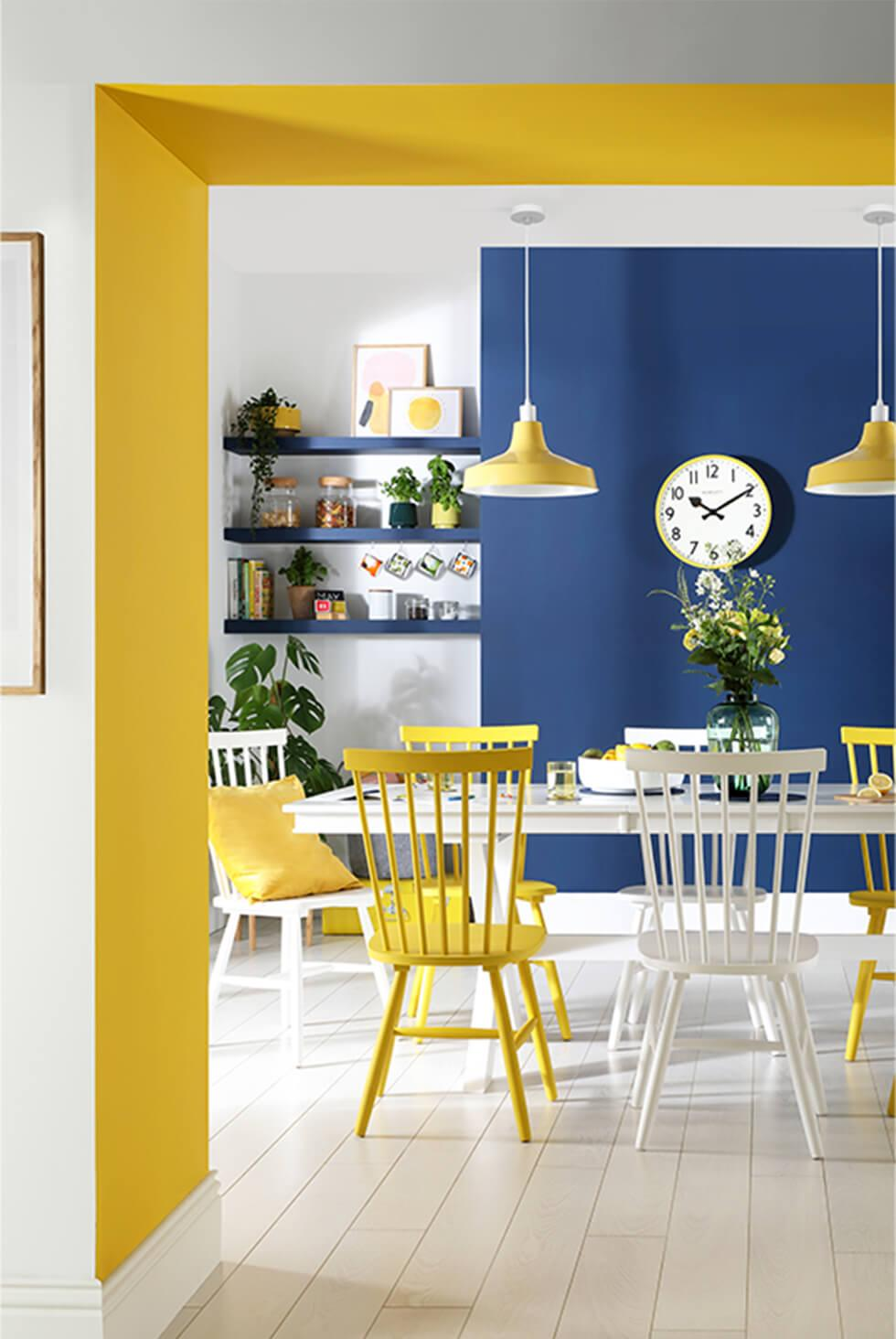 Mismatched white and yellow dining chairs with blue and yellow accent walls