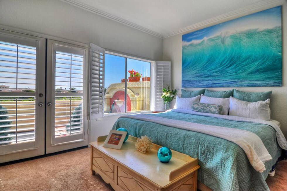 Bedroom with ocean-inspired art, teal bed and white plantation shutters
