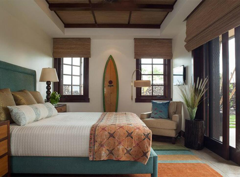 Coastal bedroom with a teal bed, dark wood and beach decor