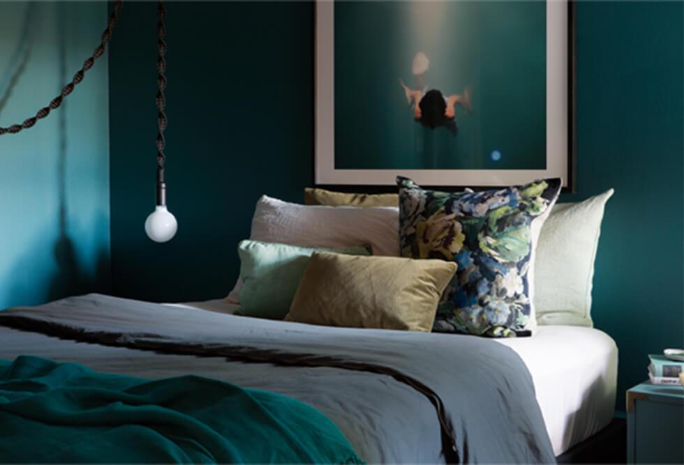 Dark, moody teal bedroom with grey bedding and simple lighting.