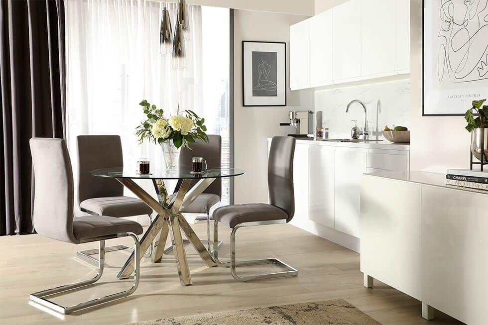 Round chrome and glass dining table in a modern lux setting