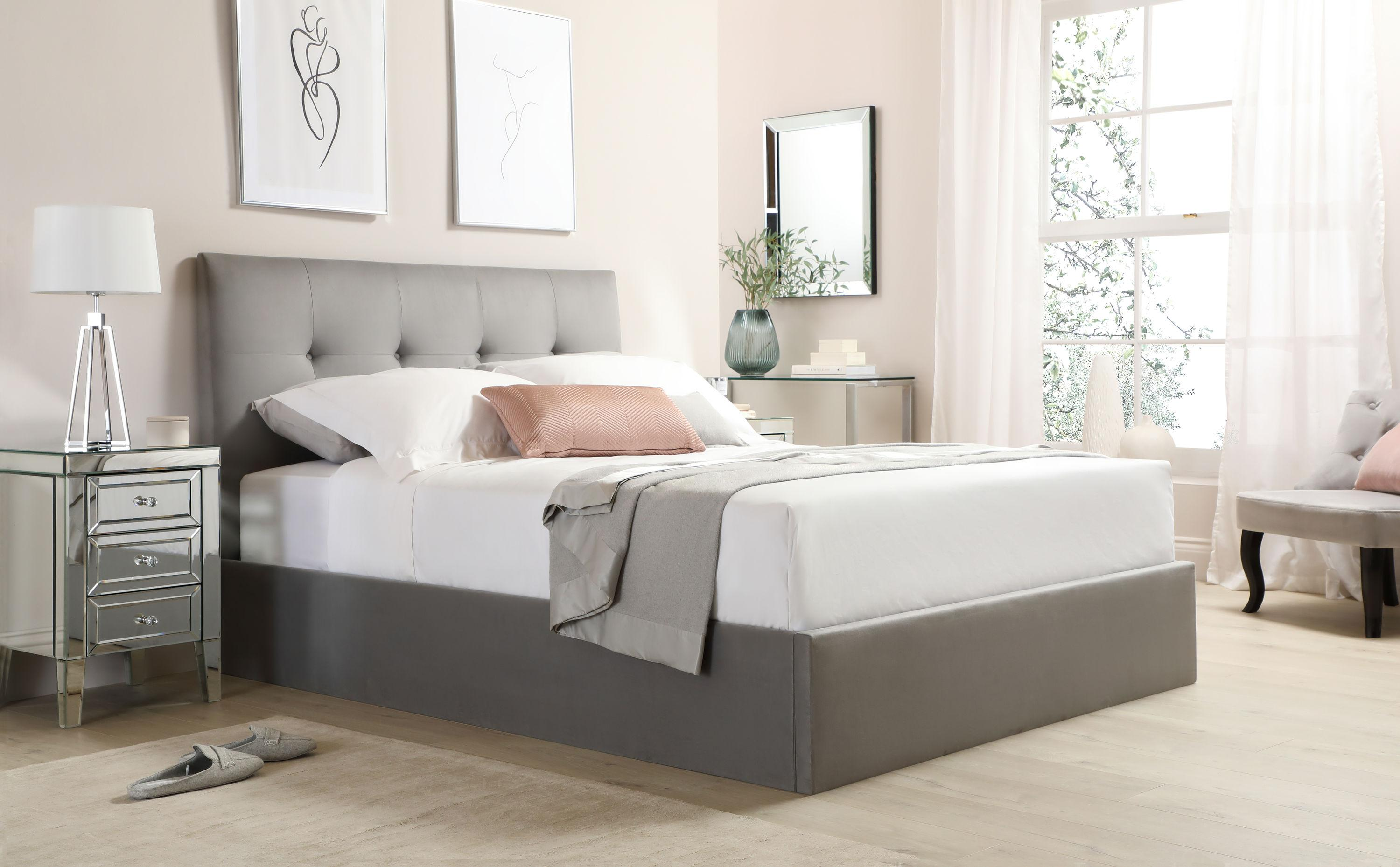 Grey velvet ottoman bed and mirrored bedside drawers in a modern and airy bedroom