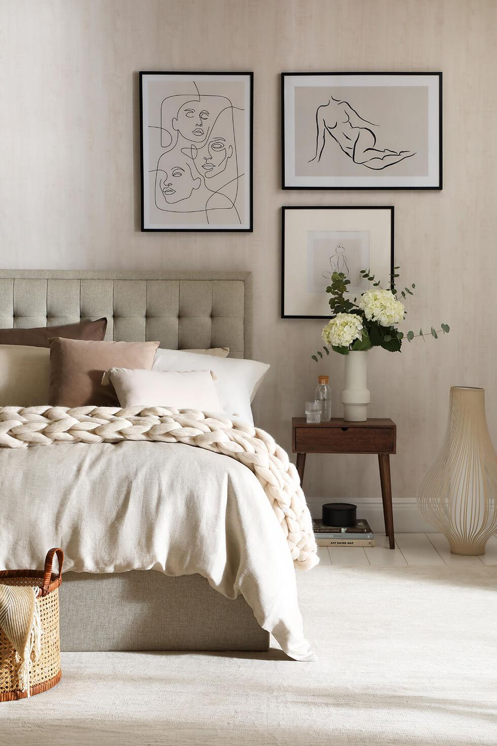 oatmeal fabric bed layered with pillows and a chunky knit throw in a cosy contemporary bedroom