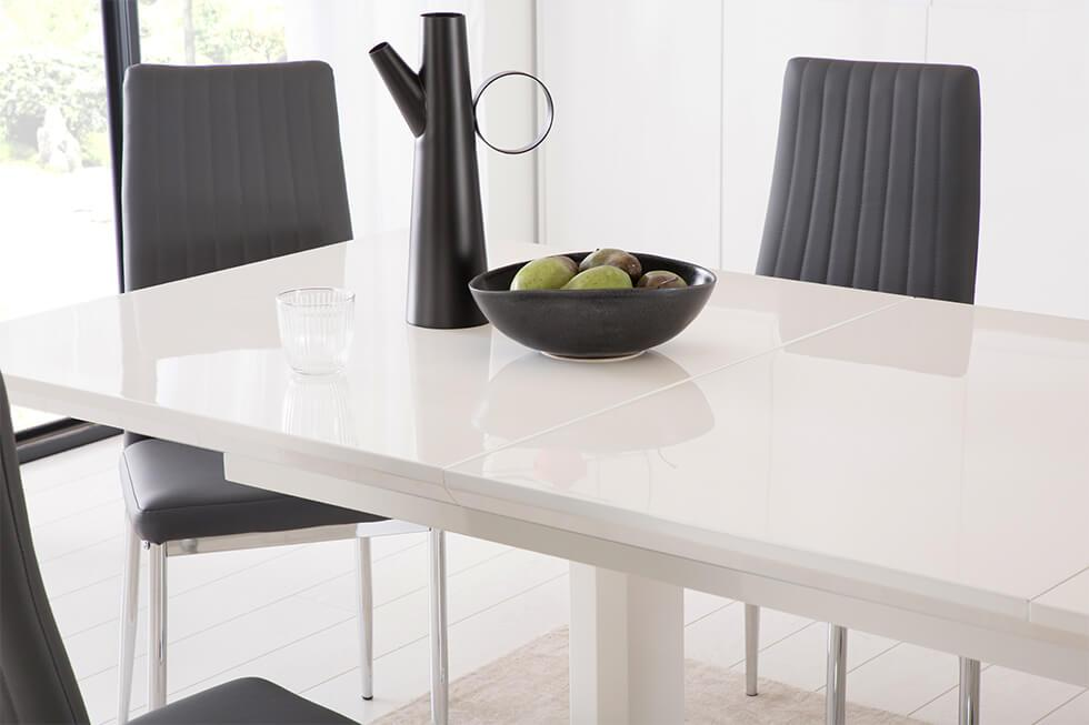 Close up of extending white high gloss dining table with black dining chairs