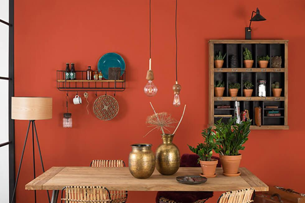Small dining room with warm orange walls, wooden dining table, shelves and bronze decor