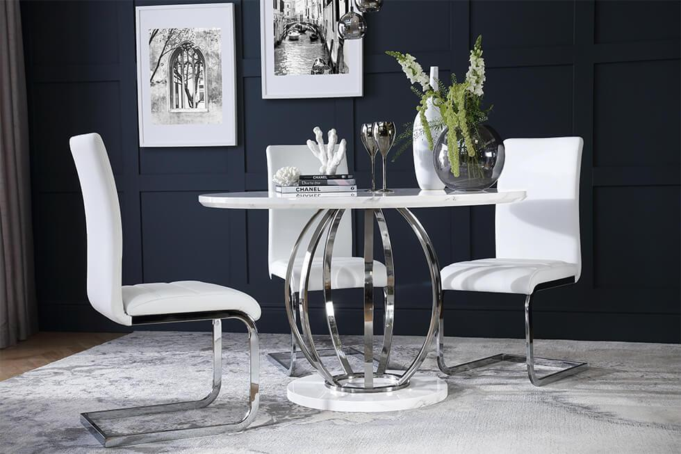 Small dining room with white marble and chrome dining table with white leather chairs against dark walls