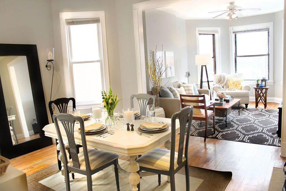 Dining room with wooden dining set, neutral tones, and a large mirror against a wall